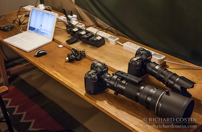 camera equipment charging with laptop processing images taken out on a wildlife photography workshop in Africa